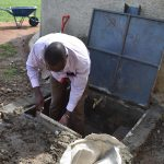 The Water Project: Mabanga Primary School -  Humphrey Plastering The Inside Of The New Catchment Area