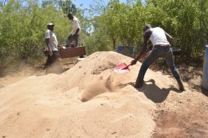 The Water Project:  Shoveling Sand That Is Used To Mix With Cement
