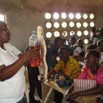 The Water Project: UBA Senior Secondary School -  Hygiene Facilitator Uses A Doll To Teach About Diarrhea