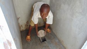 The Water Project:  Pouring Ash In The Latrine Pits