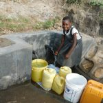 The Water Project: Shihingo Community, Mangweli Spring -  Fetching Water