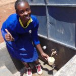The Water Project: Essongolo Primary School -  Jane Emali Enjoys Flowing Water From The Tank
