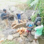 The Water Project: Munenga Community, Burudi Spring -  Community Members And Field Officer Help Out