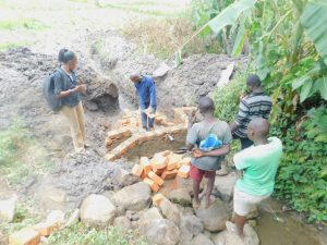The Water Project:  Community Members And Field Officer Help Out