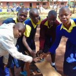 The Water Project: Essongolo Primary School -  Breaking Up Charcoal For Brushing Teeth