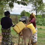 The Water Project: Kaketi Community -  Loading Water Onto Donkey