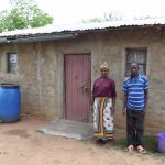 The Water Project: Kaketi Community A -  Lenah Wanza Stands In Front Of Her Home