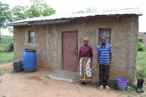 The Water Project:  Lenah Wanza Stands In Front Of Her Home