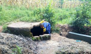 The Water Project:  Student Fecthing Water In A Covered Spring