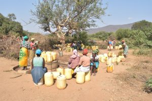 The Water Project:  Women Sit On Their Containers Waiting For Their Turn To Fill Them With Water