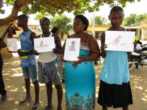 The Water Project:  Community Members Hold Training Materials