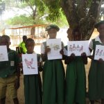 The Water Project: DEC Makassa Primary School -  Students Hold Up Posters