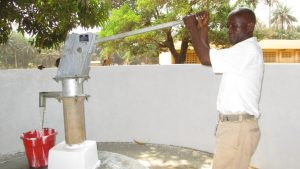 The Water Project:  The Head Teacher Pumps Water