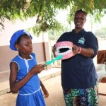 The Water Project: SLMB Primary School -  A Student Helps In The Toothbrushing Demonstration