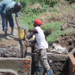 The Water Project: Mwichina Community, Shihunwa Spring -  Community Member Lends A Hand