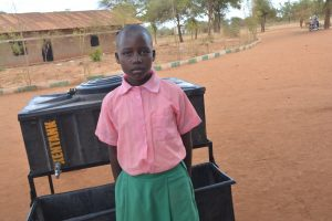 The Water Project:  Student Poses With Handwashing Station