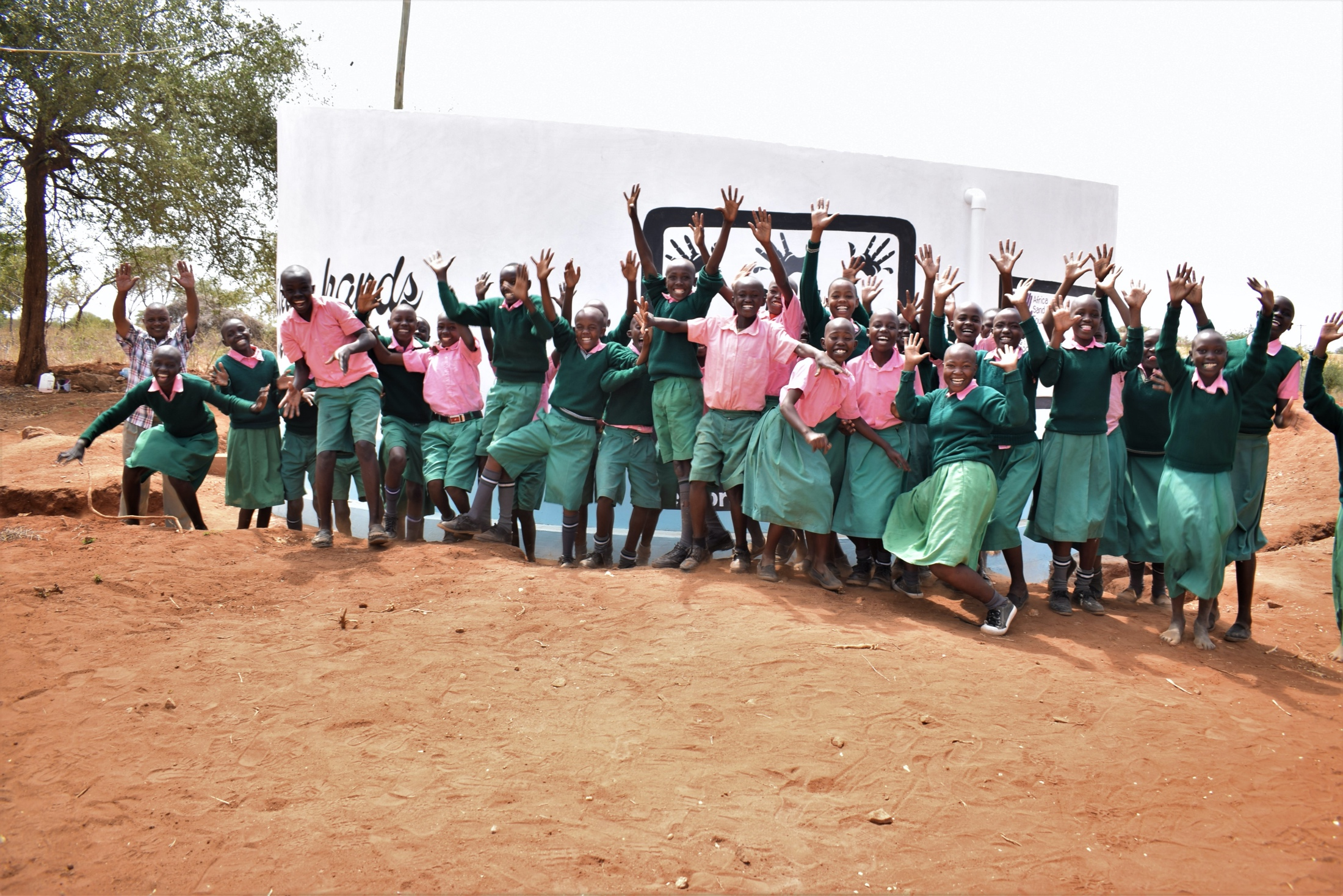 The Water Project : kenya19236-students-celebrate-in-front-of-tank
