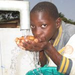 The Water Project: Tholmossor, Amputee Camp -  Young Boy Drinking Clean And Safe Water