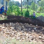 The Water Project: Kapchorwa Primary School -  Students Bring Stones For Tank Foundation