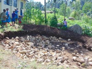 The Water Project:  Students Bring Stones For Tank Foundation