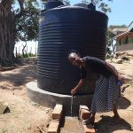 The Water Project: Mwichina Primary School -  Teacher With Five Thousand Liter Tank