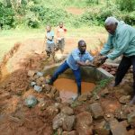 The Water Project: Mutao Community, Kenya Spring -  Backfilling With Stones