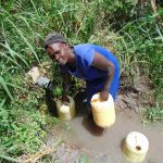 The Water Project: Bukhaywa Community, Shidero Spring -  Sarah Lumumba Fills Up