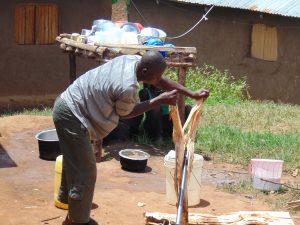 The Water Project:  Spring Landowner Mark Kipsiro Splits Wood