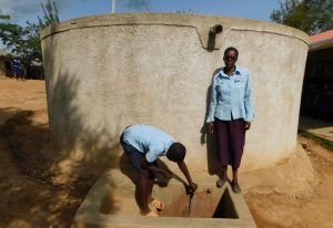 The Water Project:  Dickson Turns On The Tap Next To Teacher Mrs Sarah Oyiera Okech
