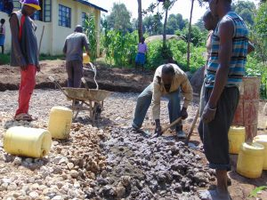 The Water Project:  Mixing Stones Into Cement For Tank Foundation