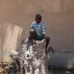 The Water Project: Mwichina Primary School -  Student Alex Sits On A Tree Trunk
