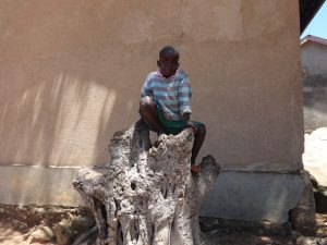 The Water Project:  Student Alex Sits On A Tree Trunk