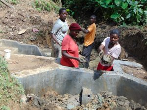 The Water Project:  Women Deliver Clay Before Backfilling