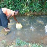 The Water Project: Bukhaywa Community, Ashikhanga Spring -  Carolyne Makhavali Fetches Water