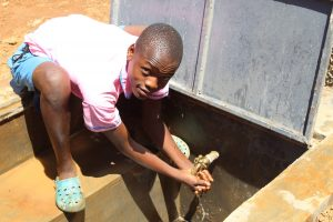 The Water Project:  Boy At Rain Tank