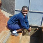 The Water Project: Ikumba Secondary School -  Student At The Rain Tank