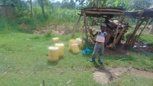 The Water Project:  Child And Water Containers