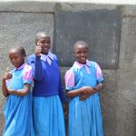 The Water Project: Kapchorwa Primary School -  Girls Posing With Rain Tank