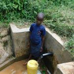 The Water Project: Maganyi Community, Bebei Spring -  Glorian Fills Her Container