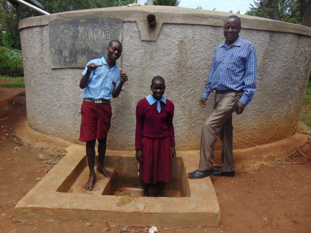 The Water Project : 3-kenya18034-mr-mango-with-students-at-the-tank