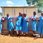 The Water Project: Irovo Orphanage Academy -  Girls Pose In Front Of Latrines