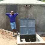 The Water Project: Kapchorwa Primary School -  Boy Poses With Rain Tank