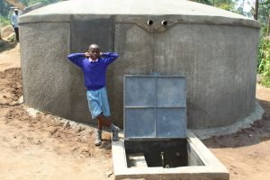The Water Project:  Boy Poses With Rain Tank