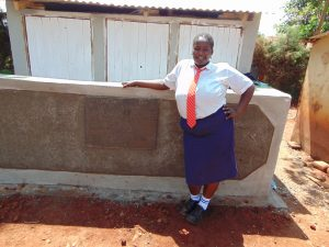 The Water Project:  Student In Front Of Latrines
