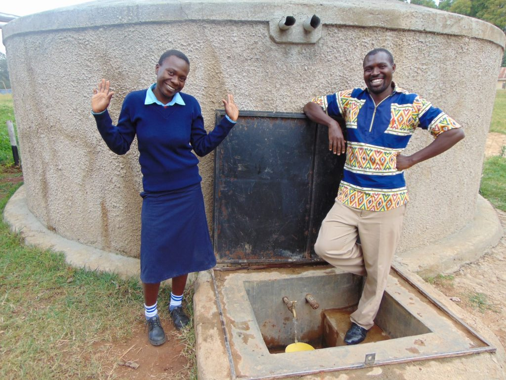 The Water Project : 4-kenya18055-rebecca-and-mr-nambisia-at-the-rain-tank