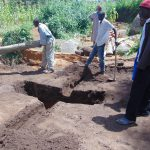 The Water Project: Kapchorwa Primary School -  Moving Logs Over Latrine Pit