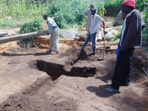The Water Project:  Moving Logs Over Latrine Pit