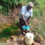 The Water Project: Mukangu Community, Metah Spring -  Selestine Fills Up