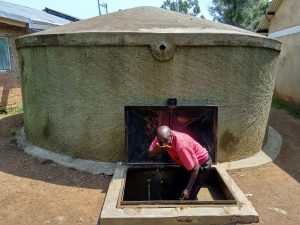 The Water Project:  Mr Maloha Takes A Drink From The Rain Tank
