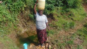 The Water Project:  Selestine Carries Water Home